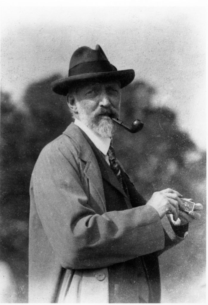 photo of a man smoking a pipe outside