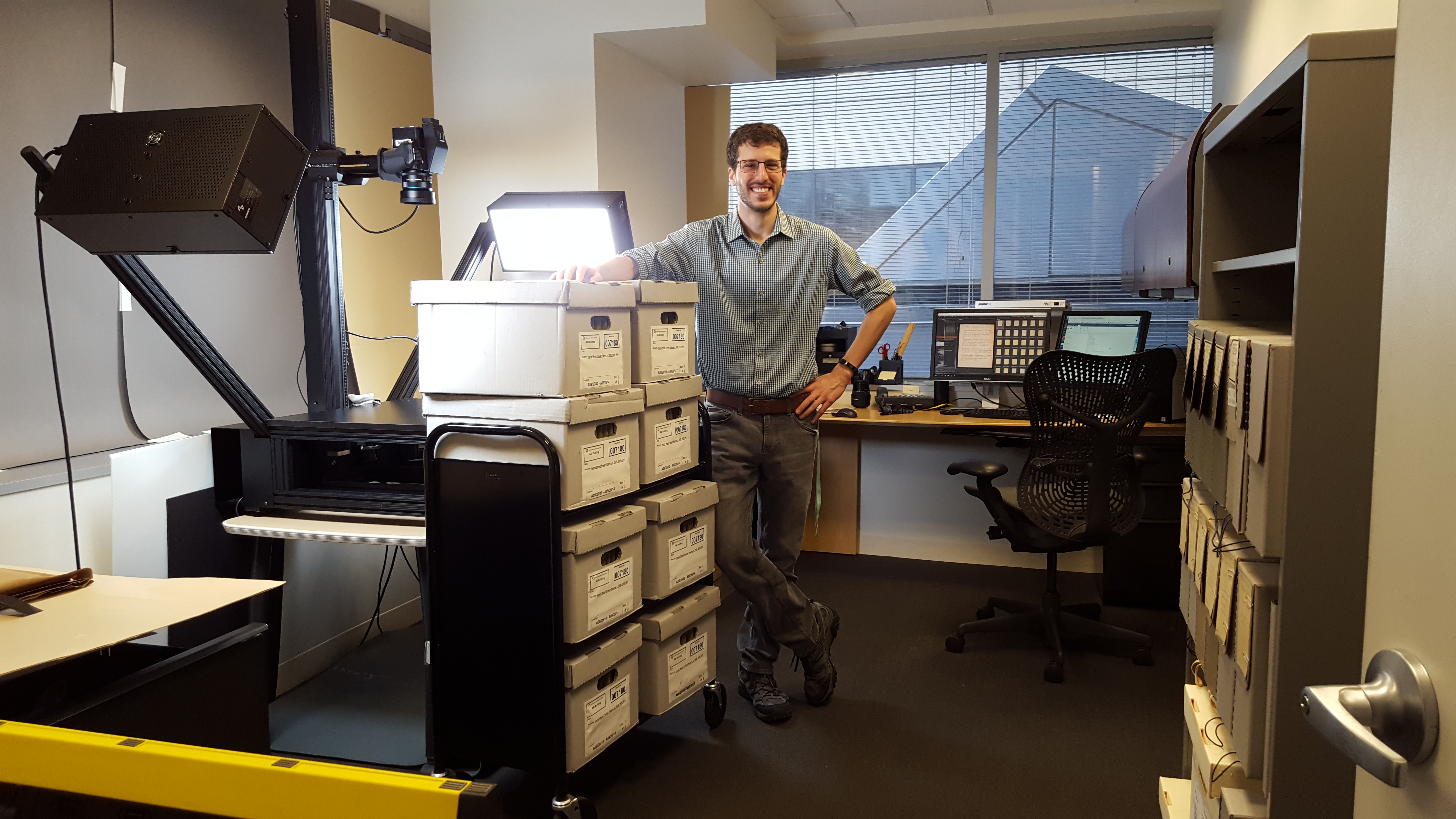 Fowler's unpublished manuscripts in the digital imaging lab, with imaging tech Charles Zange for scale. Photo by Mignonette D. Johnson. Smithsonian Institution Archives.