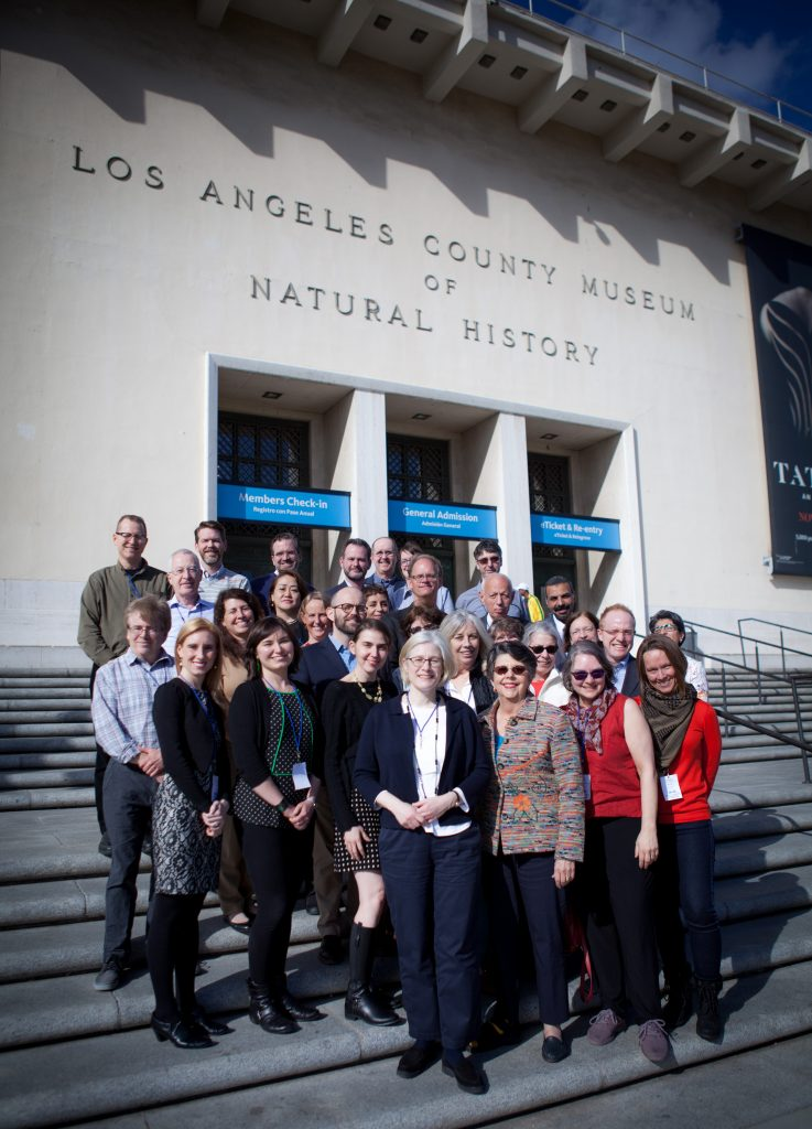 "group of men and women standing in front of a white building labeled ""Los Angeles County Museum of Natural History"""