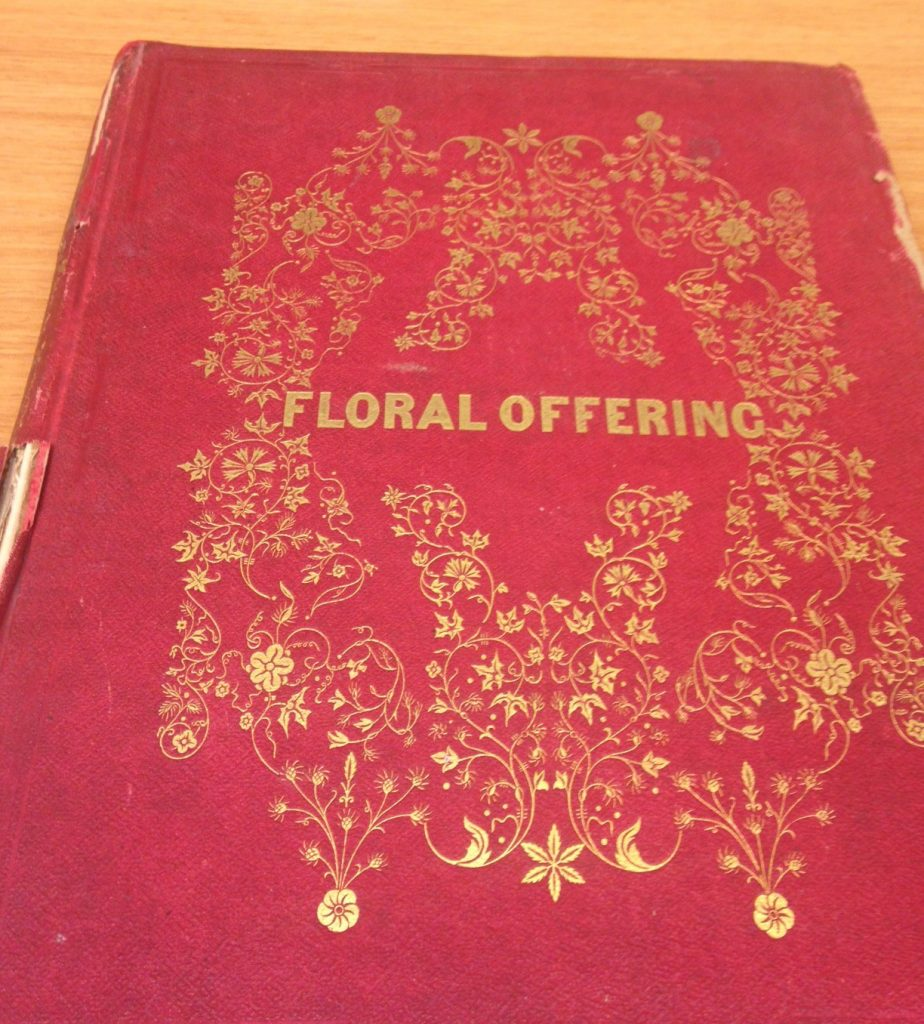 book with red binding and imprint of gold flowers