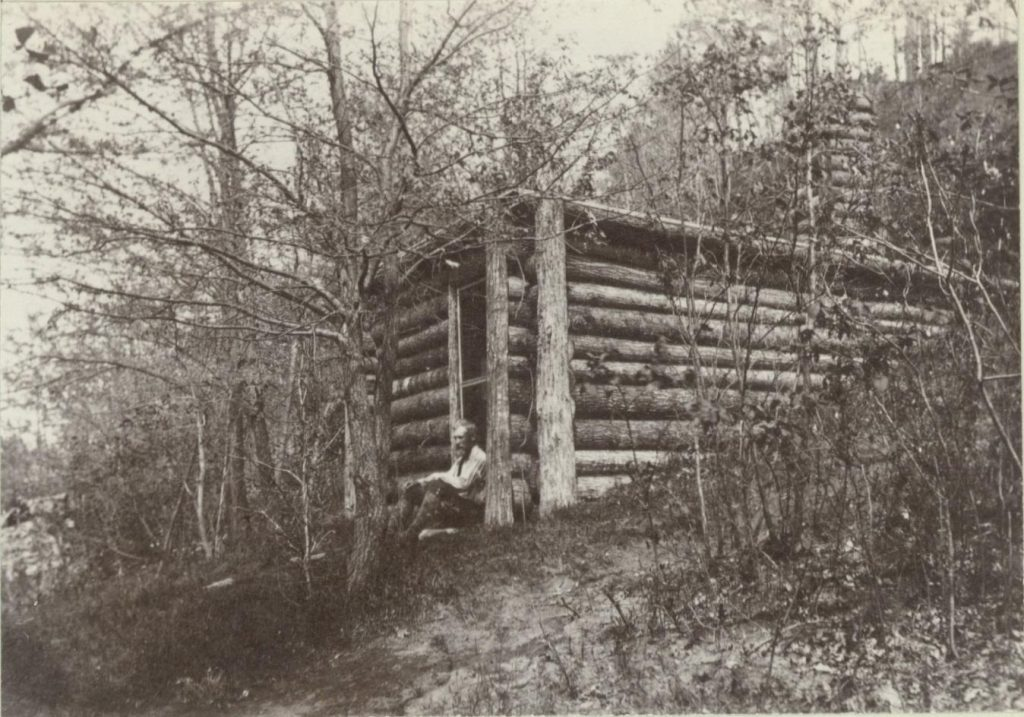 black and white photo of a man sitting in front of a cabin in the woods.