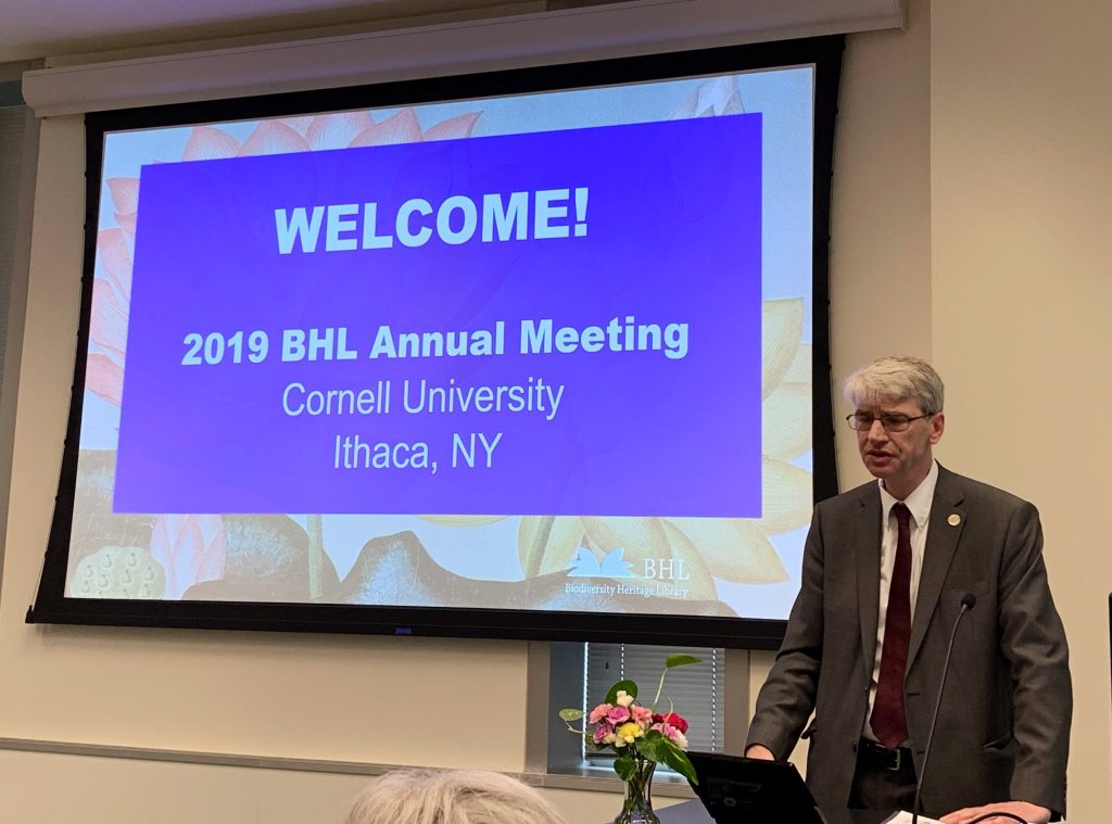 "Man in suit standing in front of a slide that reads ""Welcome! 2019 BHL Annual Meeting, Cornell University, Ithaca, NY"""