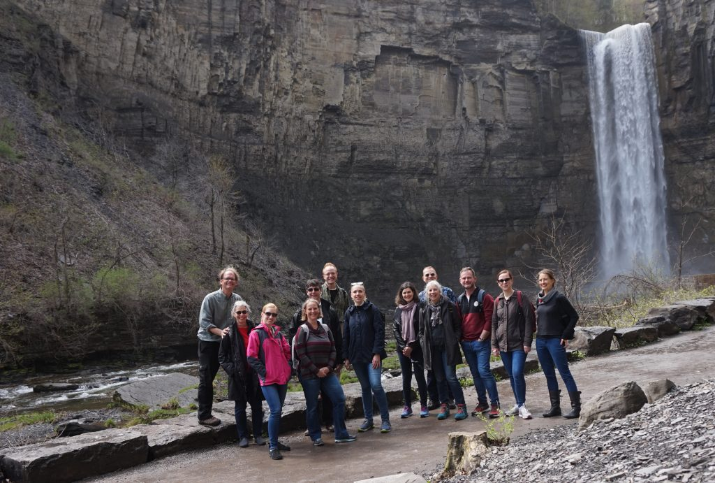 Group of people standing in front of a waterfall.