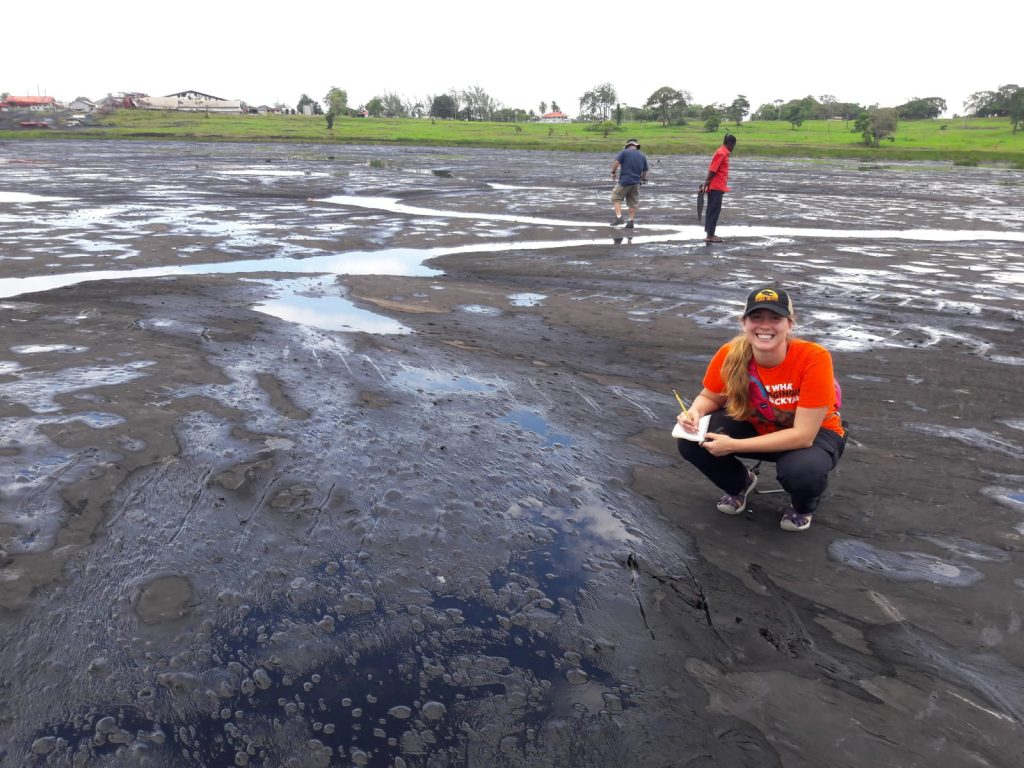 Photo of a woman kneeling by a tar pit.