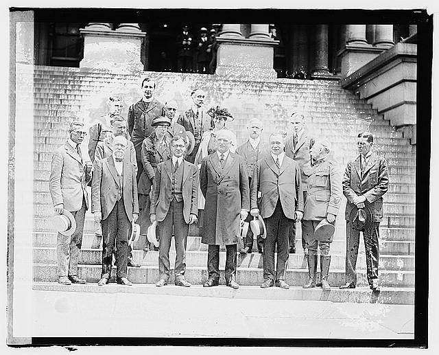 Black and white photograph of a group of men standing on steps.