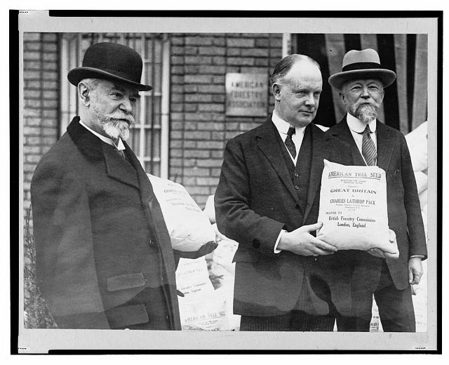 "Black and white photograph of three men, one holding a sack of seeds with the text ""American seeds to reforest France and Great Britain."""