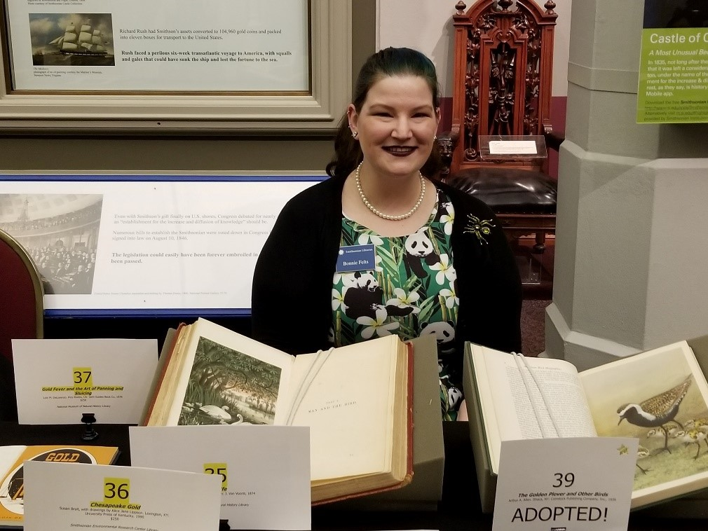 woman standing in front of a display of natural history books