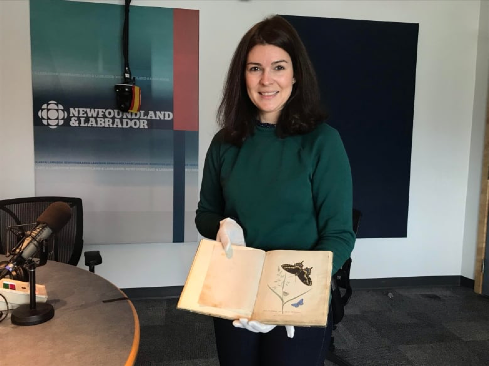 photo of a version with dark hair and green sweater holding a manuscript with illustrations of butterflies