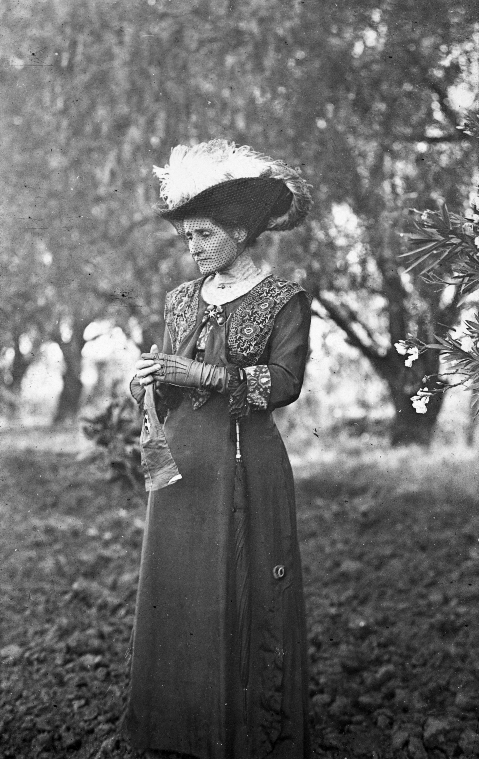 Black and white photograph of a woman in Victorian dress with an elaborate hat adorned with bird feathers. She stands in a forest.