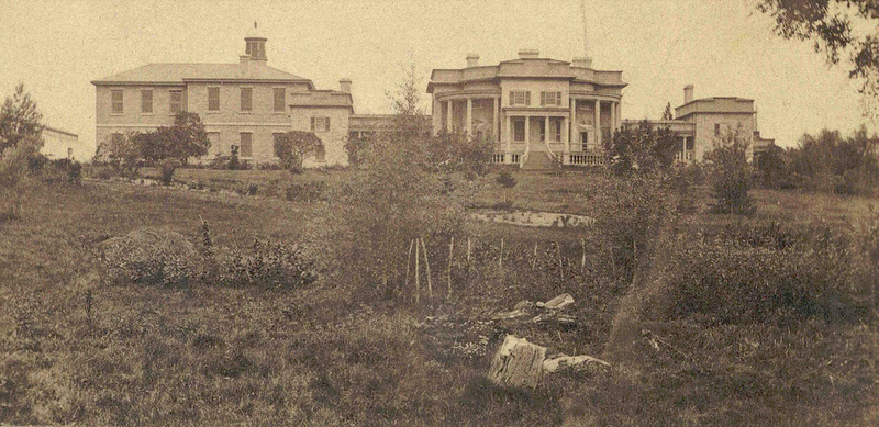 Black and white photo of victorian buildings in a garden
