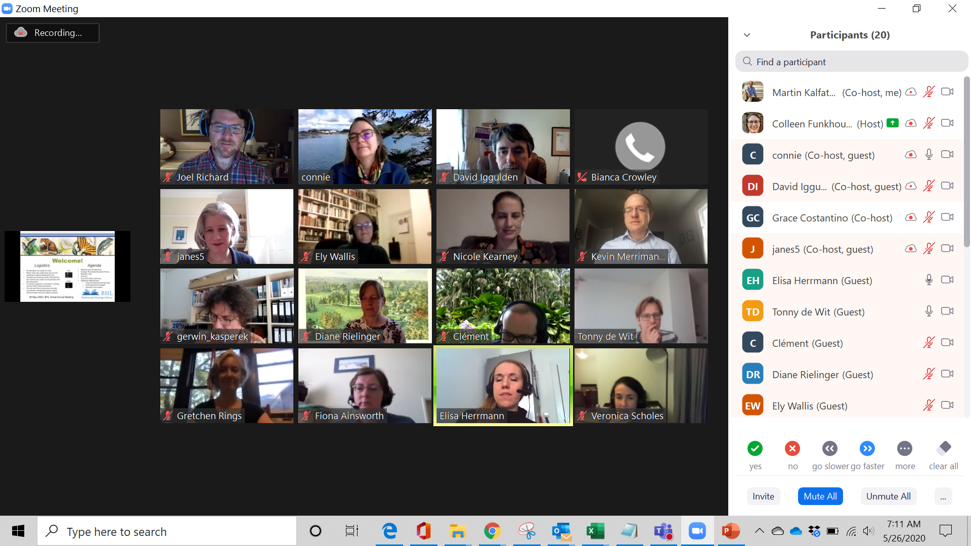 Video conferencing screen showing a grid of people's faces in video screens and a welcome slide