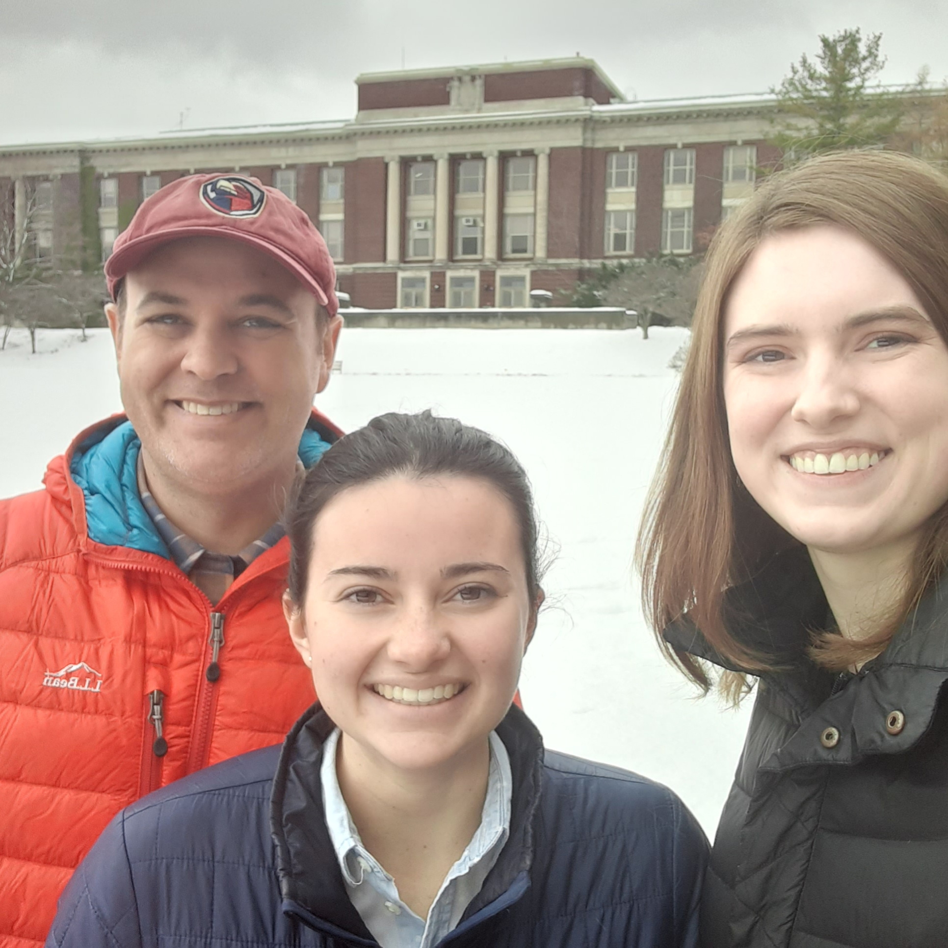three people standing in the snow with a brick building in the back