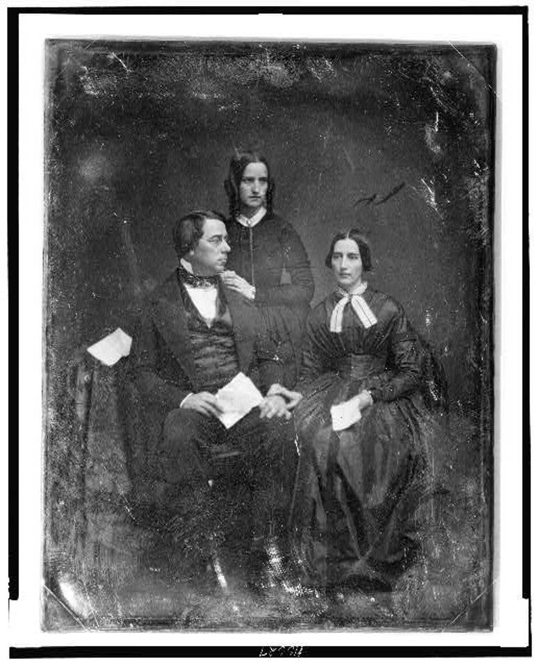 George Perkins Marsh family. Marsh seated beside a table with tablecloth, on the left, his head turned to the right, wearing spectacles, his wife seated on the right, her hand on his, her head slightly to the left, both holding papers; Caroline's sister, Lucy Crane, standing behind and between them, her hands on her brother-in-law's shoulder, her head three-quarters to the right] https://lccn.loc.gov/2004664023