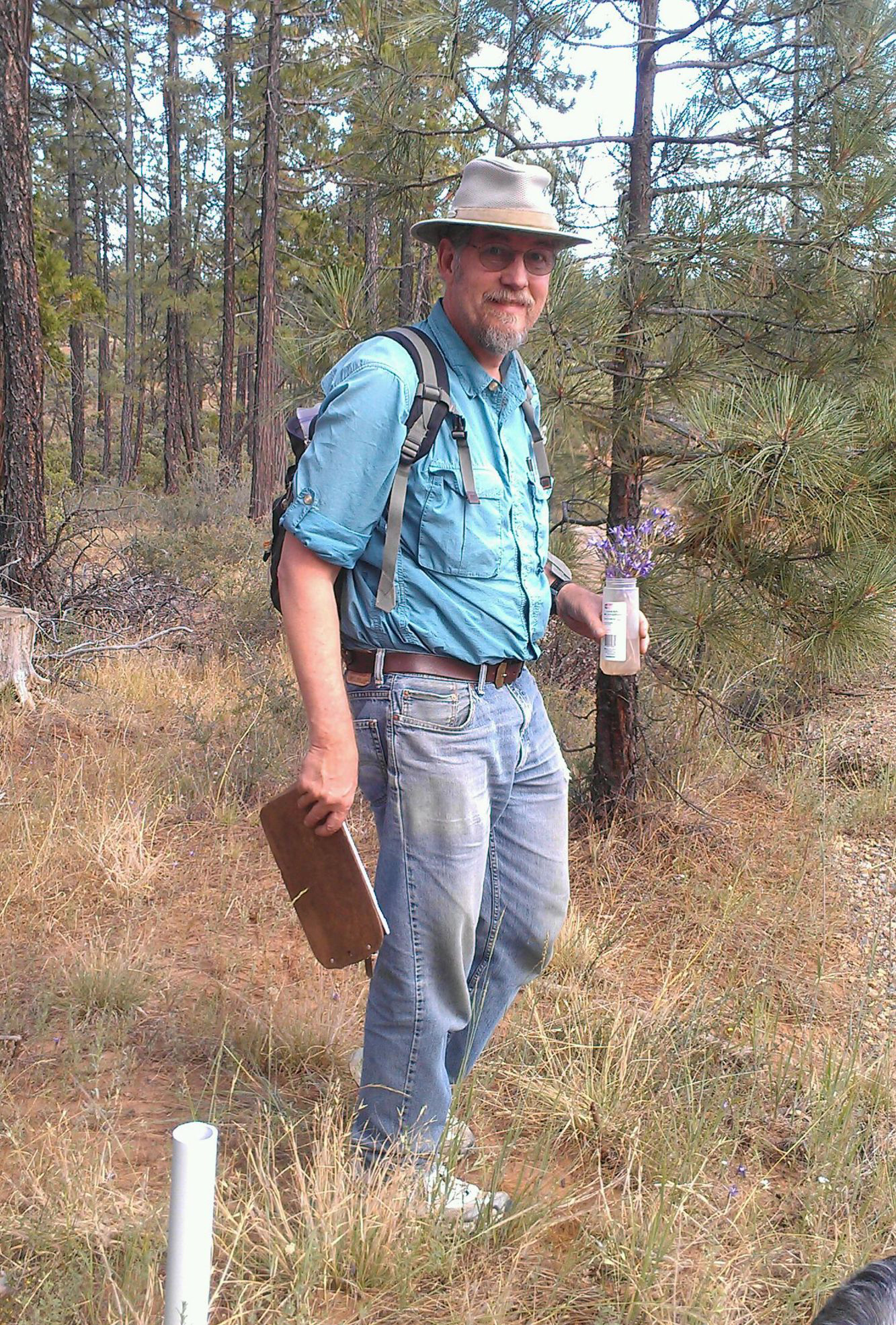 man in blue shirt, grey pants and khaki hat in a forest