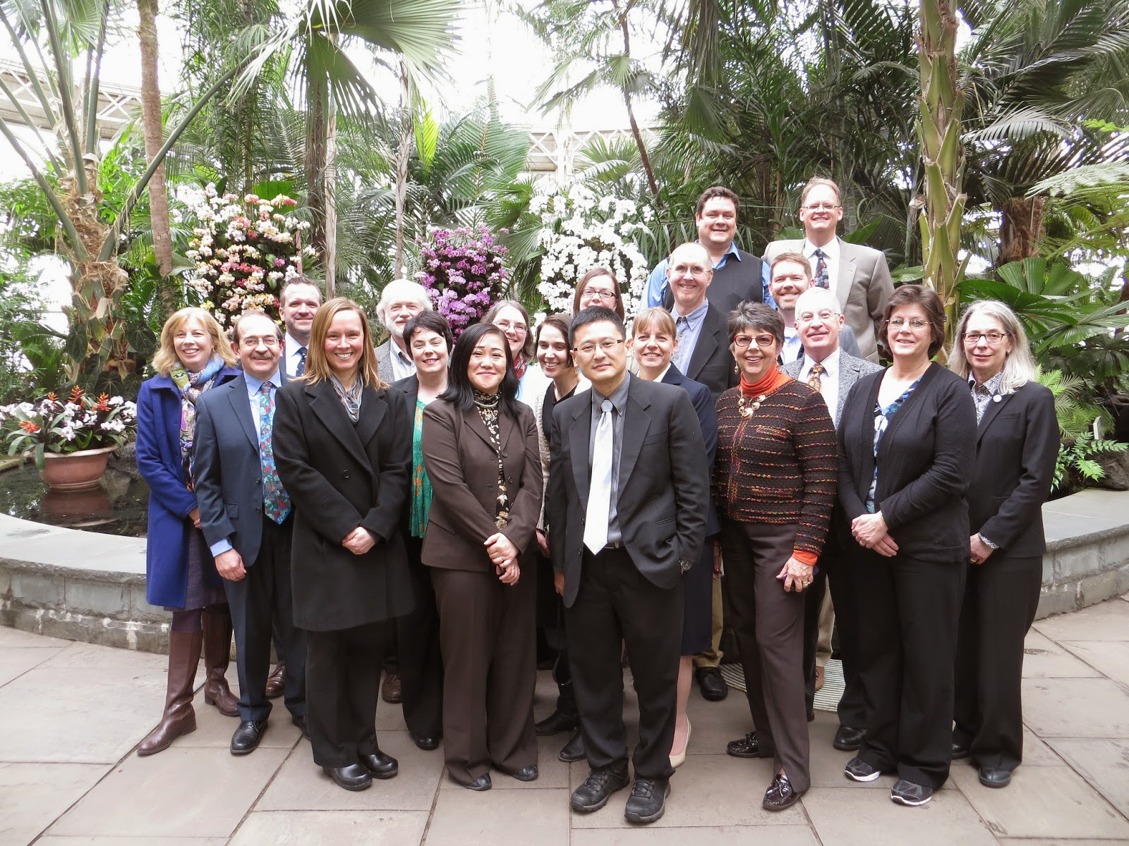 A group of people standing outside in front of a tropical garden of plants.