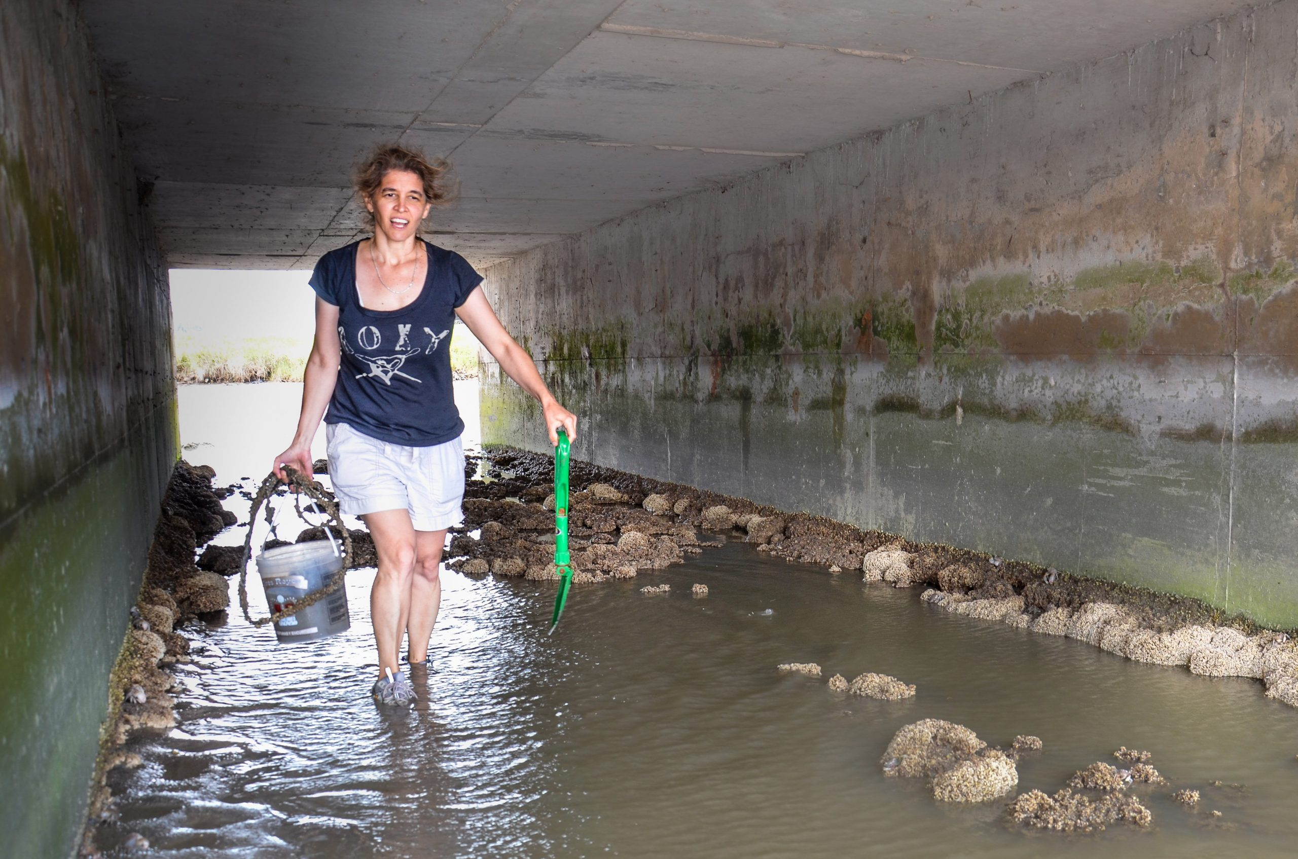 A woman in a blue shirt and white shorts walking through a tunnel with ankle high water.