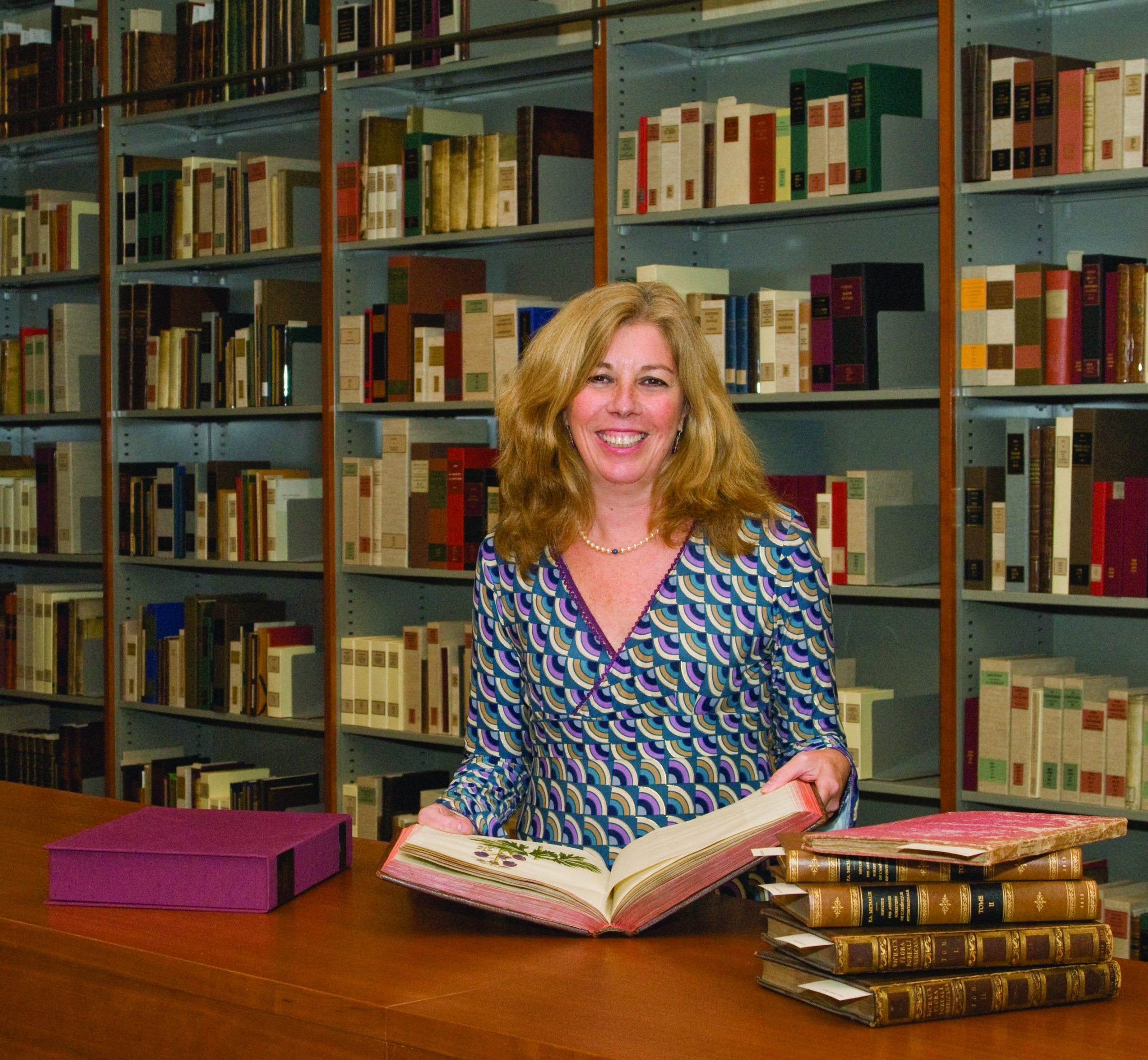 A person with shoulder length blonde hair standing in front of a large wooden table holding open a large book with a plant illustration. A pile of books is on the table next, and a bookshelf full of books is in the background.