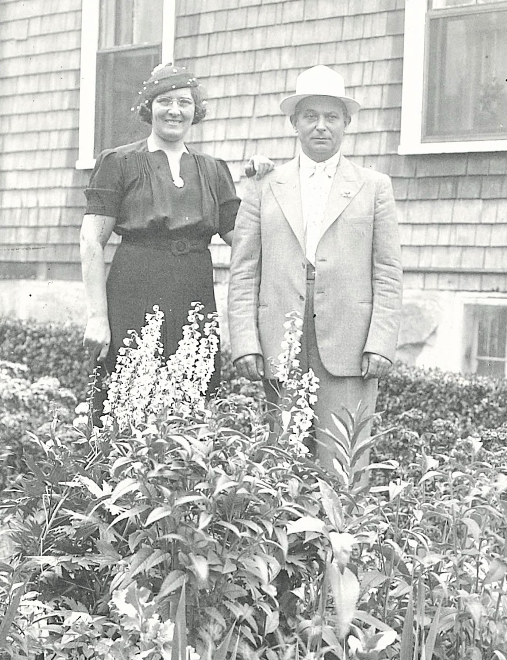 black and white photo of a woman and a man standing in a garden outside of a house.