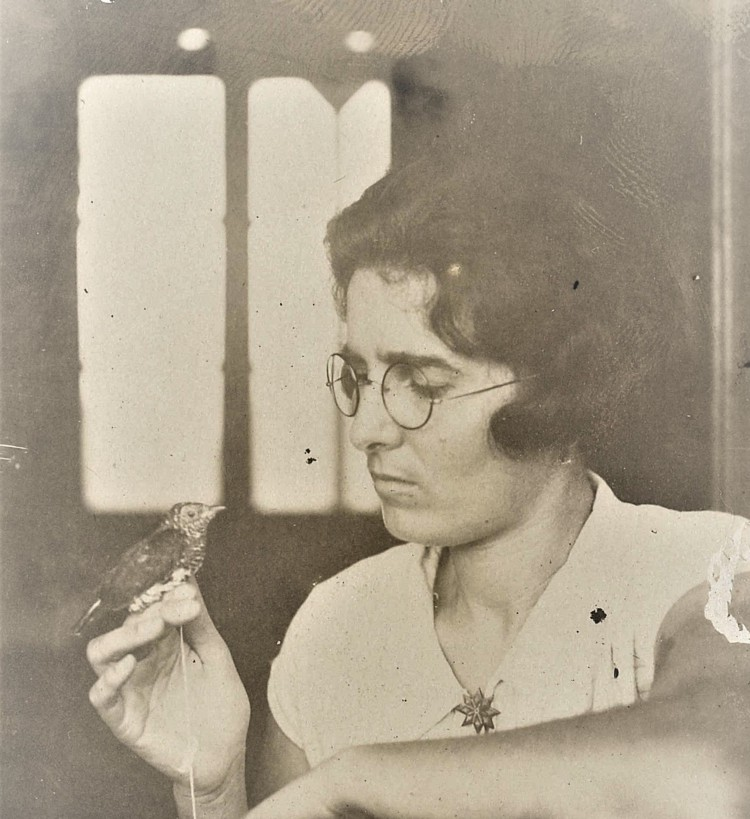 Black and white photo of a woman with short dark hair, wearing glasses, holding a bird.