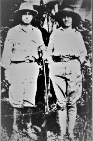 black and white photo of a man and woman in expedition clothing standing in a jungle.