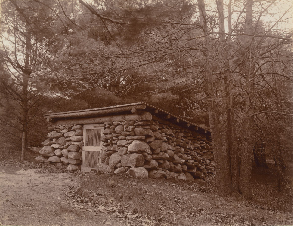 Black and white photograph of a stone wood-house in the woods.