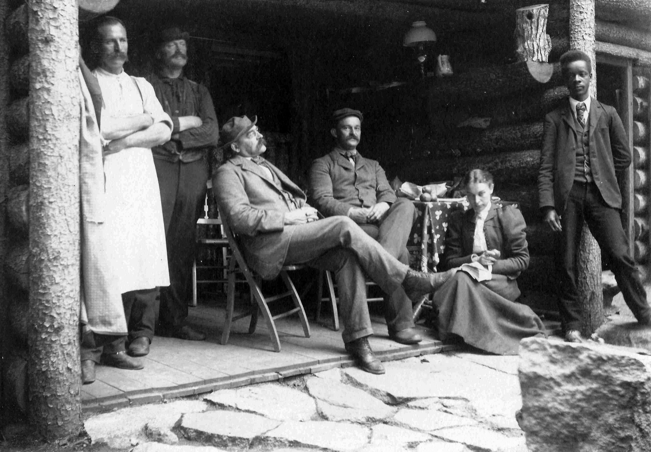 Black and white photo of a group of people standing on the porch of a log cabin.