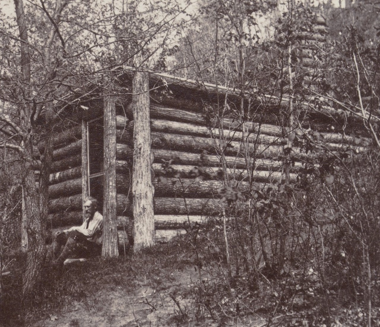 Black and white photo of a man sitting on the doorstep of a log cabin in the woods.