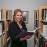 Person with red hair holding a book and standing in between book shelves.