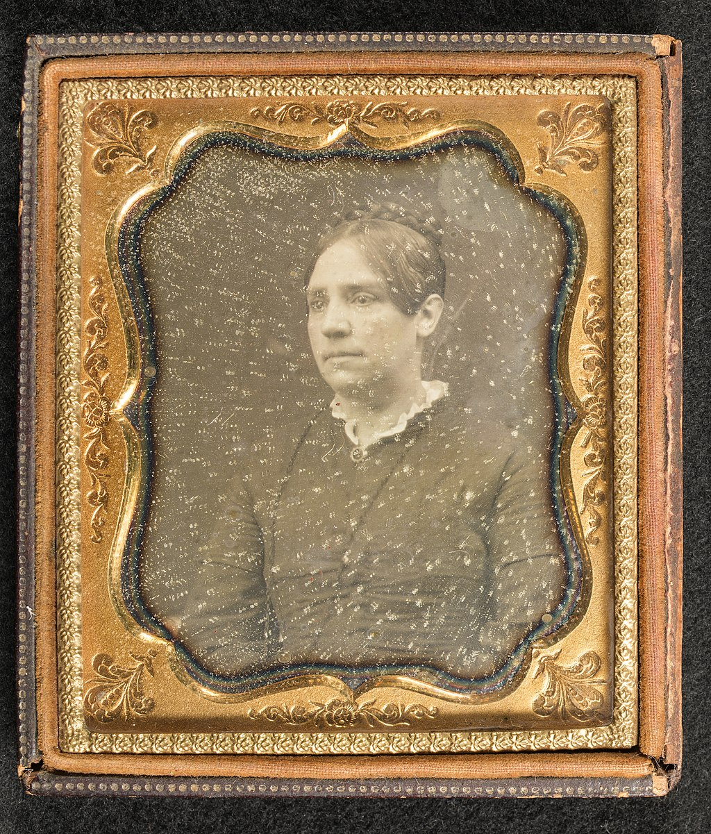 Black and white portrait of a woman in a gold frame.