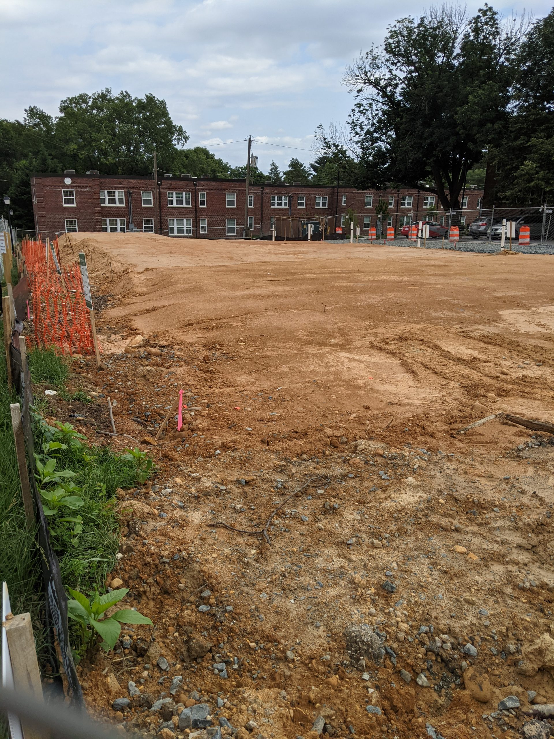 A large patch of dirt in front of a brick building.