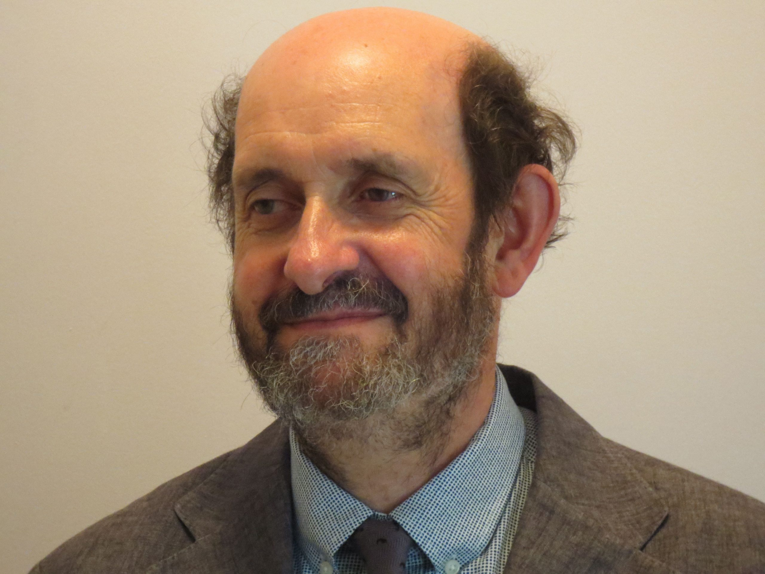 A man with a short beard wearing a brown suit jacket and blue shirt